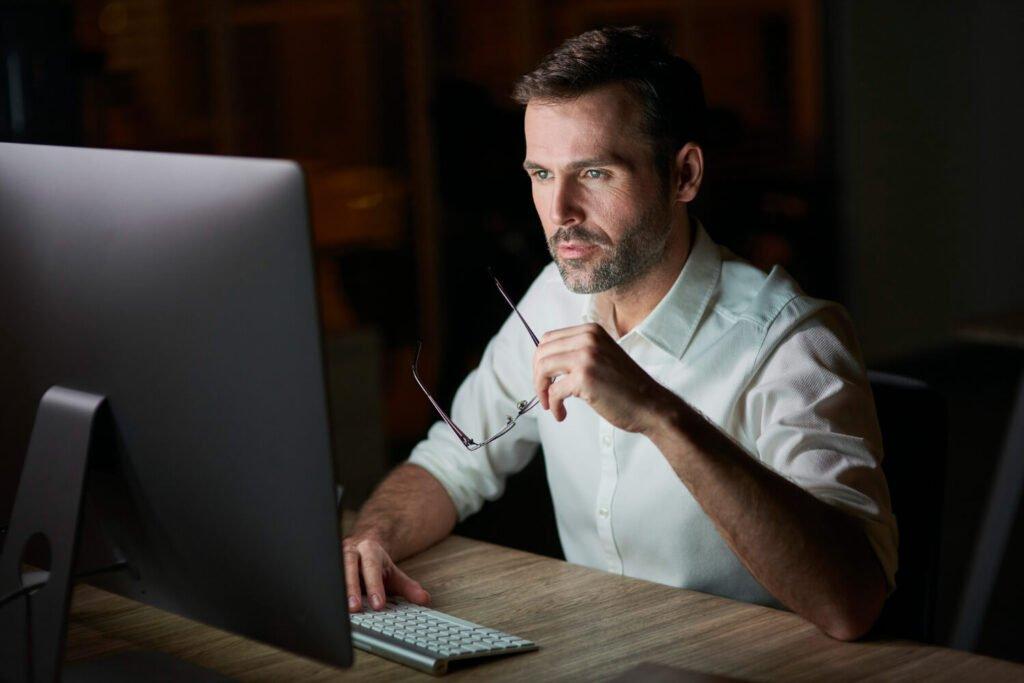 Mężczyzna przed komputerem, praca przy komputerze